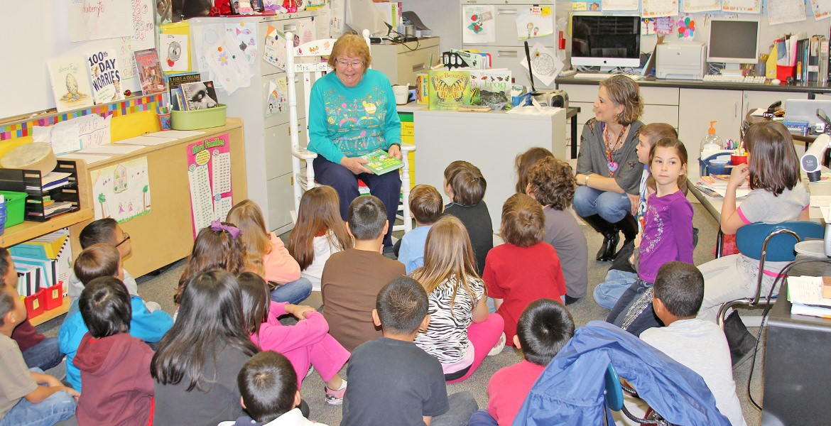 Volunteer reading to a classroom of children